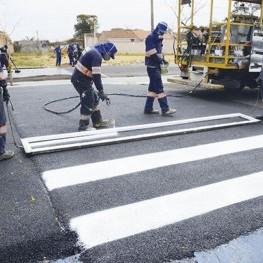 Na foto, funcionários da EMDEF realizam a pintura de sinalização da faixa de pedestres