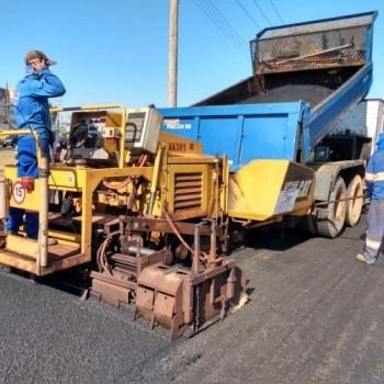 Na imagem, uma via sendo recapeada por um funcionário da EMDEF, que está operando uma máquina pavimentadora de porte pequeno e cores laranja e vermelha. Ao fundo, cavaletes de sinalização laranjas.