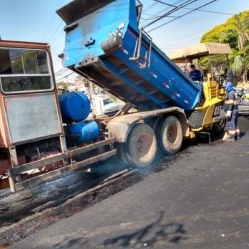 Na imagem, uma máquina pavimentadora despejando asfalto, enquanto dois funcionários da EMDEF fiscalizam a operação.