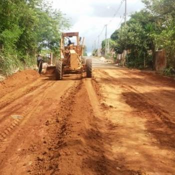 Na imagem, uma escavadeira realizando obra de terraplanagem em chão de terra.