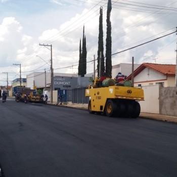 Rua recém recapeada, onde há duas máquinas operadoras, ambas de cor amarela, encostadas na calçada à direita. Também há funcionários da EMDEF, em seus uniformes azuis, com as máquinas.