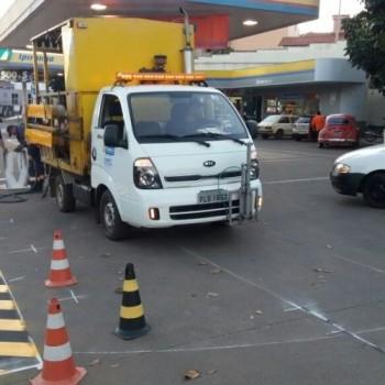 Na imagem, um funcionário da EMDEF realizando a pintura de sinalização de solo à entrada de um posto de gasolina, na cor amarela. Ao seu redor, três funcionários observando a operação e cones laranjas para sua segurança.