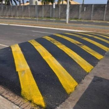 A foto mostra uma lombada recém executada na avenida, em formato de retângulo, de um lado a outro da via, em cor azul escura com faixas em amarelo. Mostra também o canteiro central da avenida, sua outra via e um muro ao fundo.