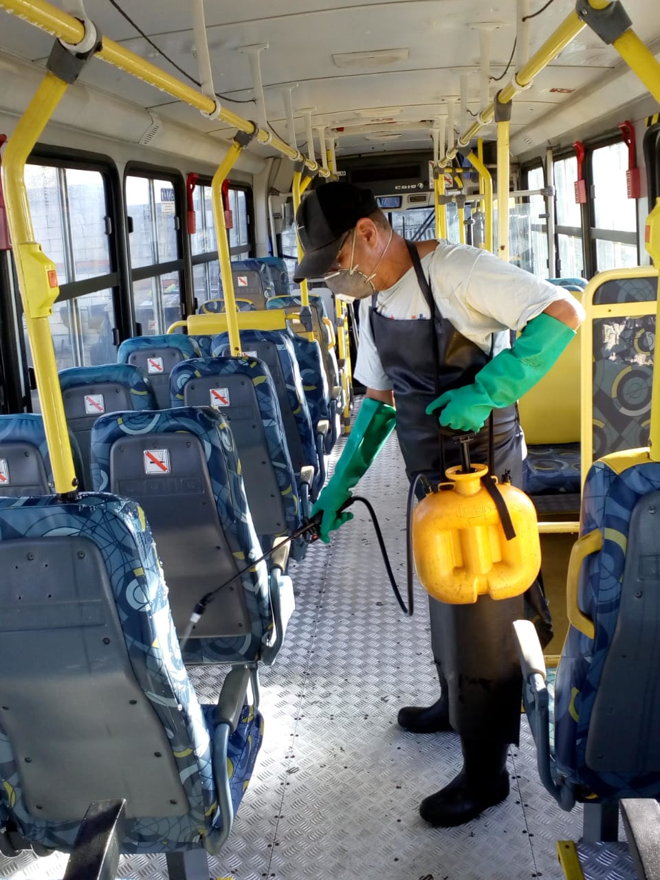 Funcionário, usando produtos de limpeza, realiza a higienização de ônibus de transporte coletivo
