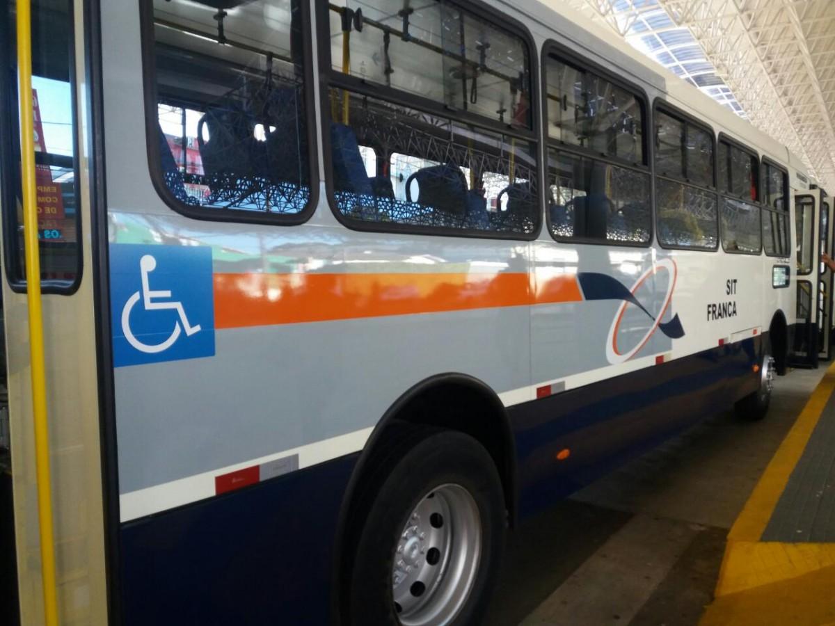 Na foto ônibus estacionado visto de lado