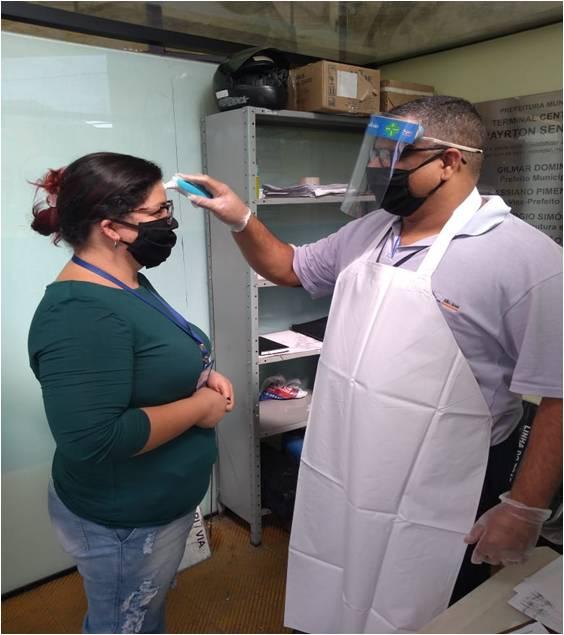 Na foto um funcionário faz a aferição de temperatura corporal de outra funcionária durante a pandemia