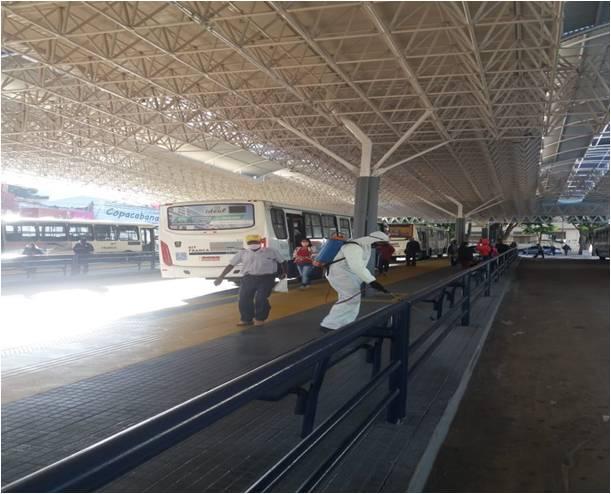 Na foto um onibus coletivo urbano está aguardando o embarque de passageiros no terminal Ayrton Senna, enquanto funcionários da EMDEF realizam a higienização do terminal
